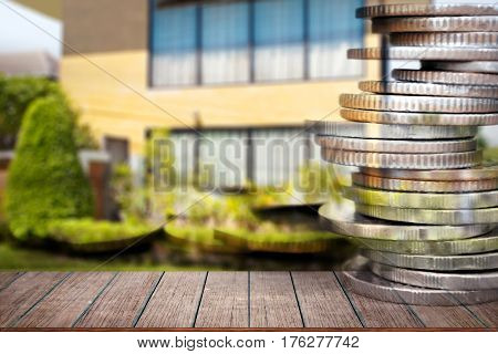 Business finance and real estate concepts Empty wood table top Money coin stack with blurred home garden background.