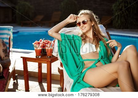 Young beautiful blonde girl smiling, sunbathing, lying on chaise near swimming pool. copy space.