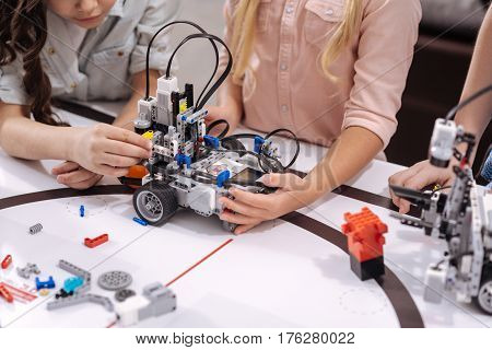 Testing tech invention together. Smart confident involved schoolchildren sitting at school and testing cyber toy while having science lesson