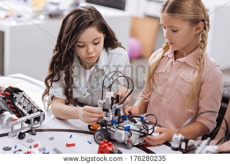 Applying new information. Skillful clever charming schoolgirls sitting at school and testing cyber toy while having science lesson