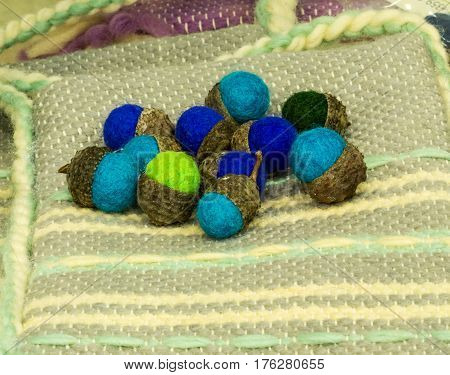 Felt souvenir handmade acorns on the rug woven by hand. Traditional crafts of Bulgaria, Eastern Europe
