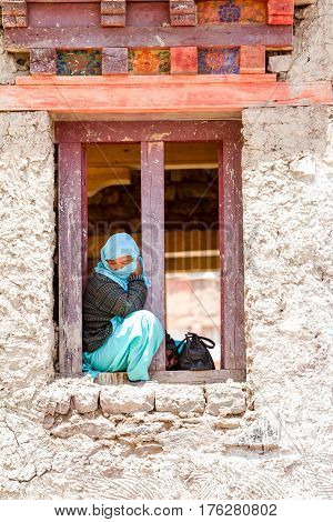 Hemis, India - June 29, 2012: Lonely covered with shawl young woman sitting in a windows span watching a religious masked and costumed Cham Dance Festival of Tibetan Buddhism in Hemis monastery India.
