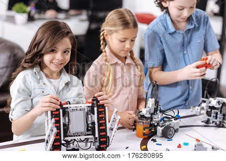 Realizing our science project. Charismatic delighted charming school children sitting at school and testing cyber devices while having science lesson