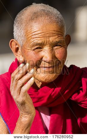 Jelichun India - 27 July, 2012: Friendly looking and smiling old buddhist nun from Jelichun nunnery in a sunny day, close-up portrait