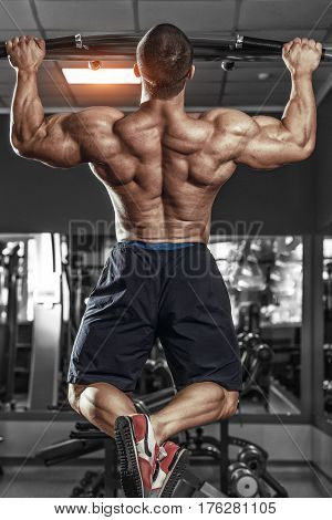 Muscle athlete man in gym making elevations. Bodybuilding