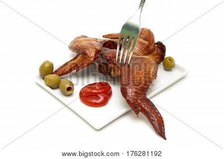 Smoked chicken wings on a plate on a white background. Horizontal photo.