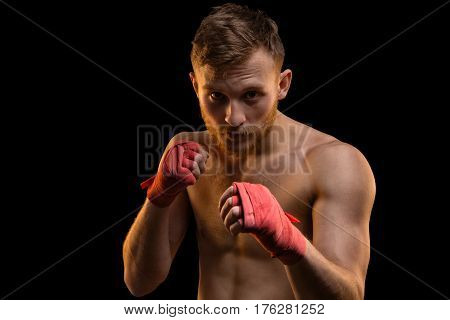 Fighter with red boxing bandages on black background