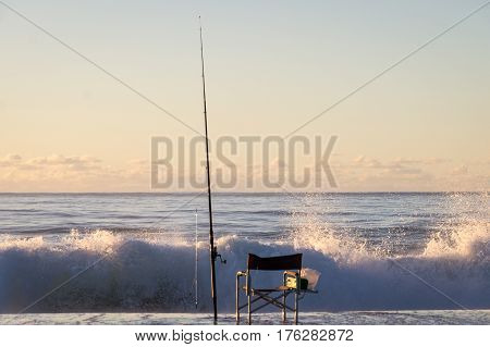 Fishermen Chair at Sunrise on beach with waves