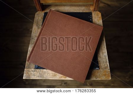 The book is an old leather cover rests on a vintage floor in the room