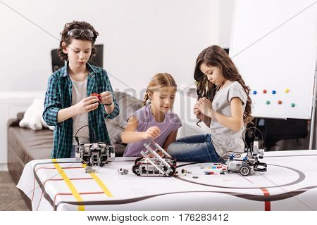 Fulfilling our responsibilities. Cute involved hardworking kids sitting in the robotics laboratory and testing cyber devices while having science lesson