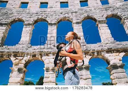 Mother With Baby In Carrier In The Old Town Of Pula, Croatia.