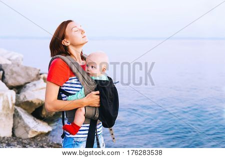 Baby and mother on the sea at summer day. Happy family walking on nature. Child in a carrier backpack