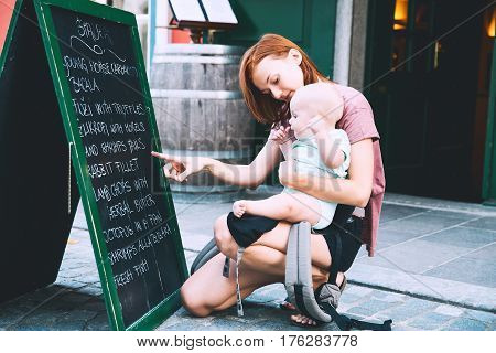 Beautiful young mother with baby child spend time in the old town of Ljubljana Slovenia Europe. Mother and son are traveling and walking in a european city.