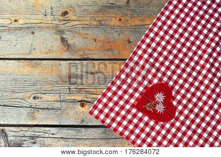 Checkered tablecloth textile on a old wooden texture table. Background photo