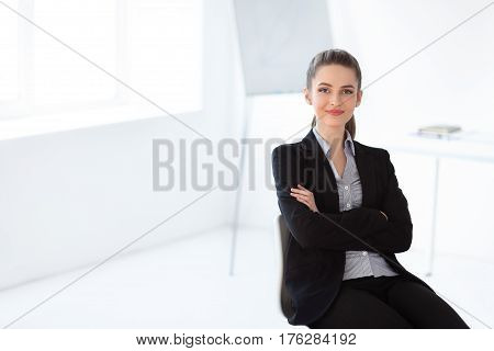 Portrait Of Young Beautiful Business Woman Sitting On Chair In The Office