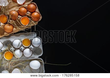 Fresh chicken eggs background. Brown and white eggs in craft carton pack on hay on black with copy space. Top view. Natural healthy food and organic farming concept.