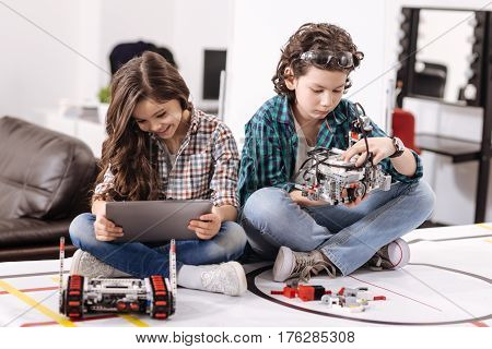 Enjoying new devices . Positive involved amused kids sitting at home and using gadgets and devices while having fun