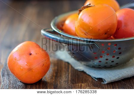 Fresh Persimmon On Wooden Table And Persimmons On Collander.
