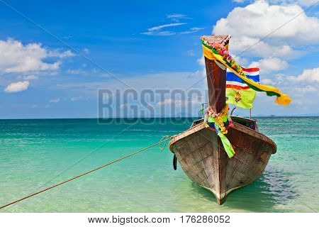 Travel background. Beautiful Thailand tropical sand beach view with decorated traditional longtail boat. Vacation day tour from Phuket to Ko Phi Phi Don island Phi Phi archipelago Krabi Andaman Sea