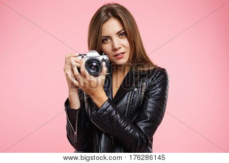 Portrait of beautiful girl posing with old roll-film camera, taking pictures of friends