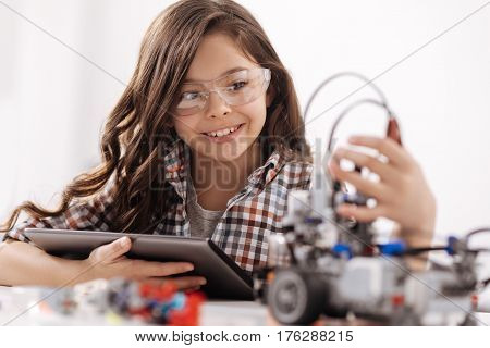 Realizing my science idea. Crafty smiling cheerful girl sitting in the science studio and using devices while studying