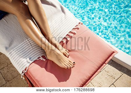Beautiful girl lying on chaise near swimming pool. Close up photo of legs.
