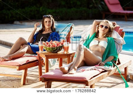 Young beautiful girls sunbathing, relaxing, resting on chaises near swimming pool. Copy space.