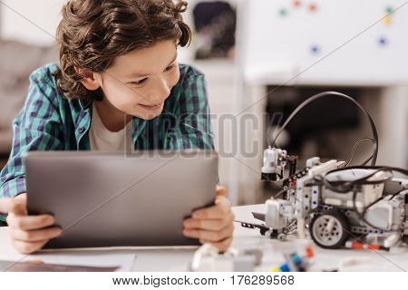 Getting acquainted with new electronic friend. Outgoing delighted cheerful boy sitting at school and using digital gadget while studying and expressing joy