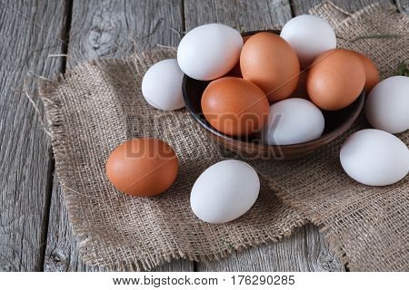 Poultry farm concept. Fresh brown and white eggs on burlap sacking textile at rustic wood background. Rural still life, natural organic healthy food.