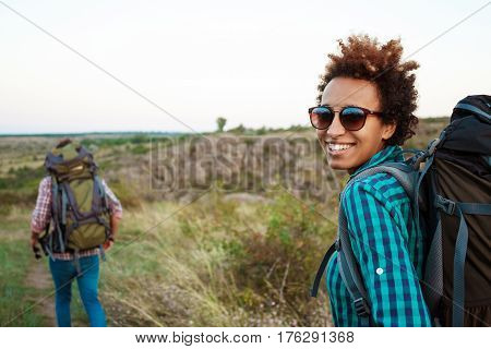 Young beautiful african girl in sunglasses with rucksack smiling, looking at camera, friend traveler  background. Copy space.