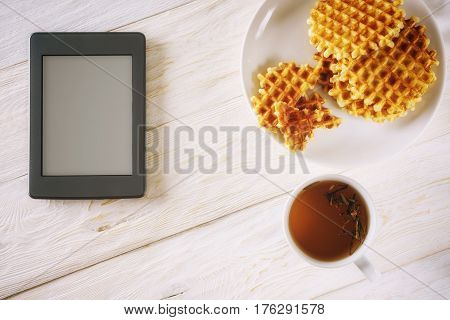 Cup of tea, waffle and ebook. Copyspace