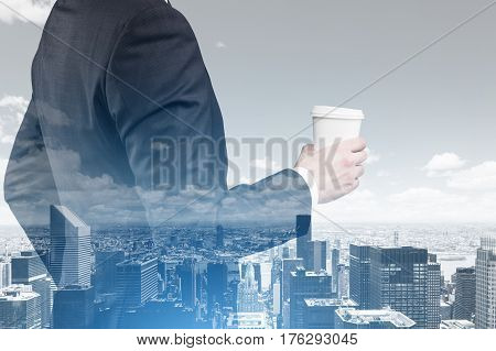 Double exposure of a cityscape and a businessman with cup of coffee looking at the skyscrapers in front of him. Double exposure