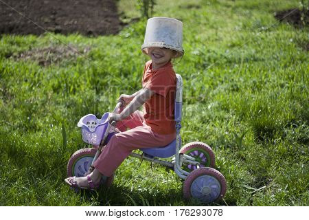 Cute girl playing outdoors with a bike and an old bucket