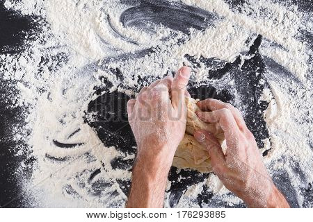 Baking concept. Flour, milk, butter, yeast and eggs carton on rustic wooden table, cooking ingredients. Unrecognizable man's hands top view knead dough on black background, copy space. Male baker