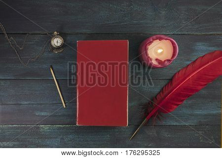 A mockup with a blank red book cover, a vintage chain watch, a burning candle, a match, and a quill pen
