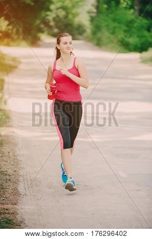 young athletic girl perfoms exercises in the gym running sports and exercieses in the park