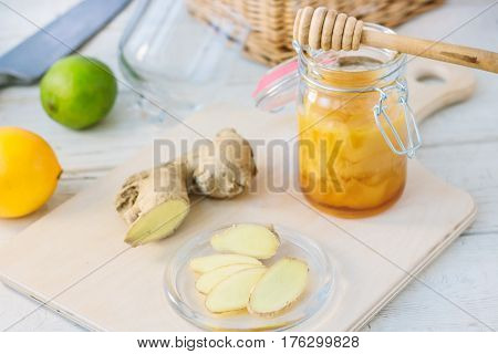 Slices Of Ginger And Honey Over Wooden Board.