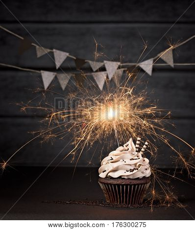 Chocolate cupcake with lit sparkler on a dark background.