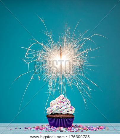 Birthday cupcake with sparkler and sprinkles over a blue background.