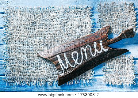 Burlap frames on blue painted wood boards. Dark wooden cutting board with text 'Menu' as title bar. Structured shabby style background for natural food and drink industry