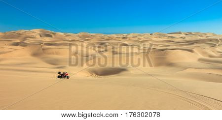 Quad driving in sand desert. ATV in the middle of nowhere. Panoramic desert view. Africa.