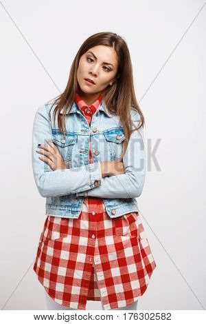 Young funny woman in basic outfit, white jeans, check shirt, denim jacket making silly faces