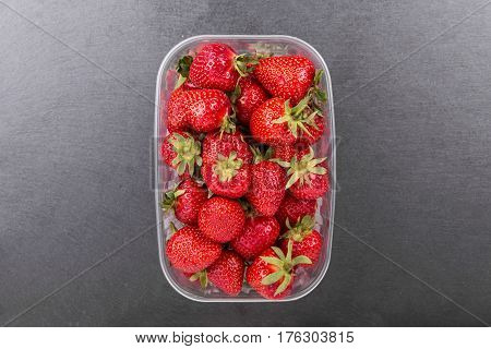 Strawberries in plastic box on a slate board top view