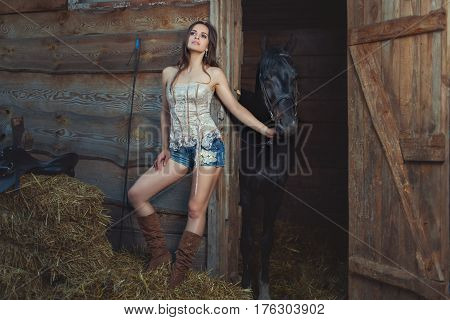Woman holds a horse for a bridle she has a pensive face.