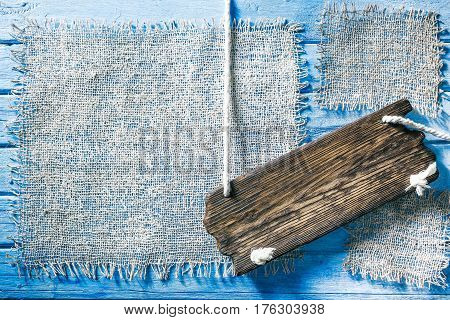 Burlap frames on blue painted wood boards. Dark wooden signboard on ropes as title bar. Structured shabby style background for natural food and drink industry