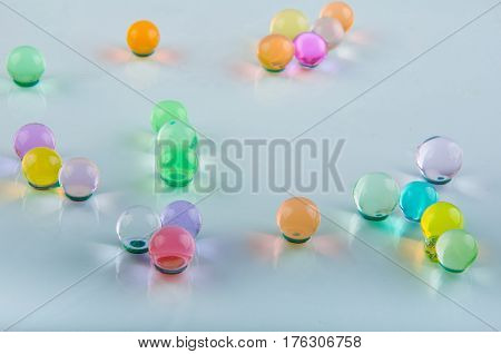 colored hydrogel balls lay on white background poster