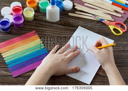 The Child Draws The Details. Present For St. Patrick's Day Clover On A Rainbow, A Craft Of Of Wooden