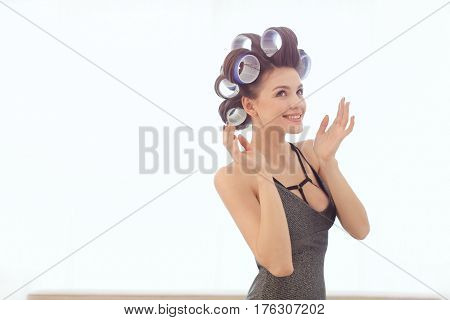 Girl in hair curlers in sexy dress and day make-up on white background. Portrait of a sexy woman preparing to party indoors at home against bright window. Young model happy smiling and looking away