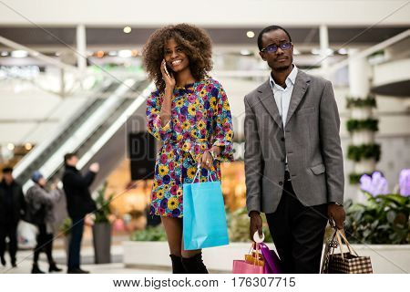 Afro-american woman and man walking together after shopping with bags in hands.