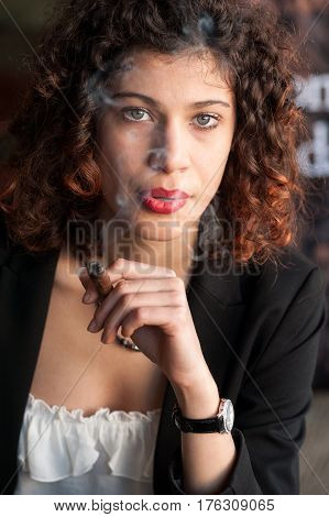 A beautiful young woman with blue eyes enjoing a Tuscan cigar looking into the camera